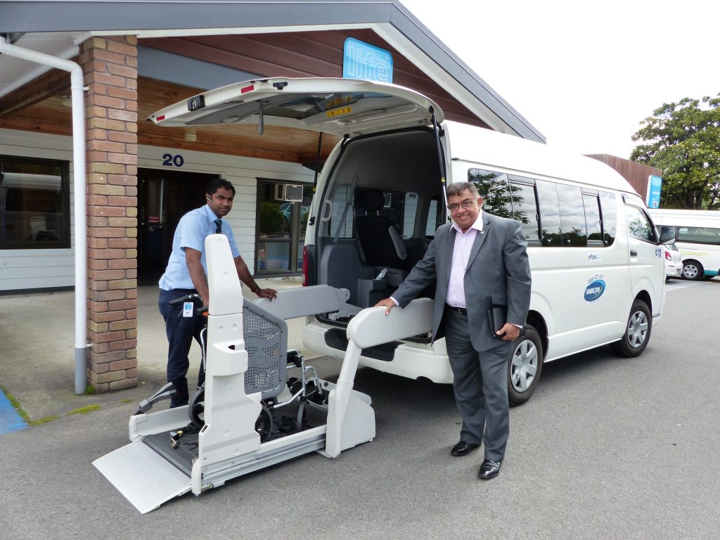 Taxi driver Bharat Reddy operates power lift on a mobility van with Andy Collins from Hamilton Taxis